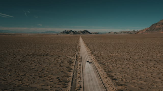 drone shot flying downwards and towards a truck driving along a dusty dirt road in a remote mountainous landscape, nevada, united states of america - nevada stock videos & royalty-free footage