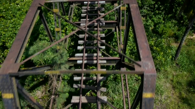 drone shot flying over a disused metal rail bridge in togo. - metal clip stock videos and b-roll footage