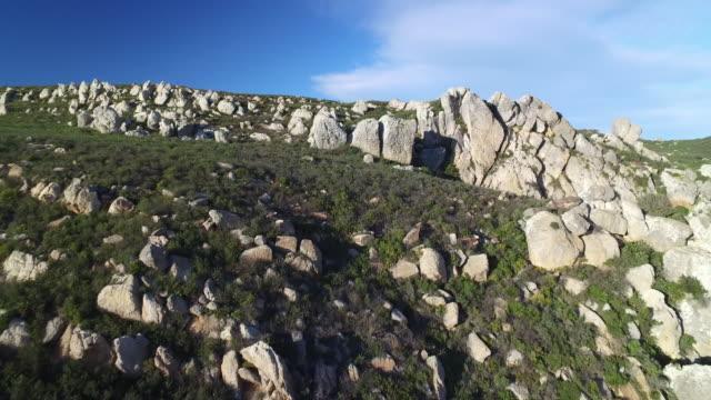 Drone shot flying over rock strewn hills in the La Breña y Marismas del Barbate Natural Park, Cadiz, Spain.