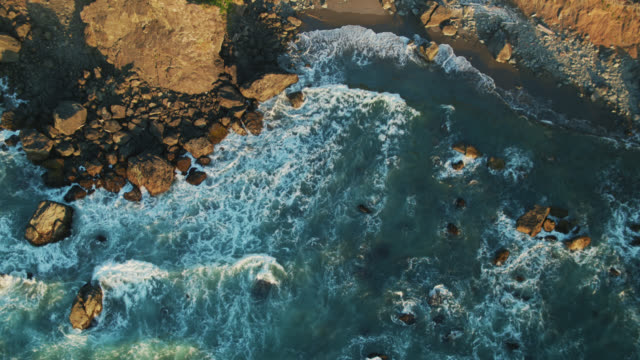 drone shot flying over swirling pacific waters towards cliffs of oregon coast - oregon coast stock videos & royalty-free footage