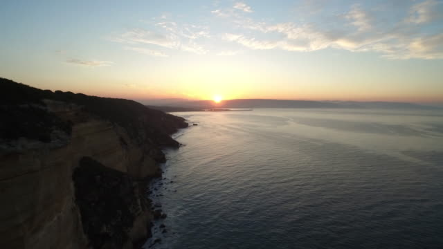 Drone shot flying over the beautiful coastline of the La Breña y Marismas del Barbate Natural Park at dusk.
