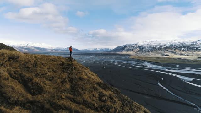 vídeos y material grabado en eventos de stock de drone shot flying past a hiker standing on the edge of a mountain looking at the view, iceland - paisaje espectacular