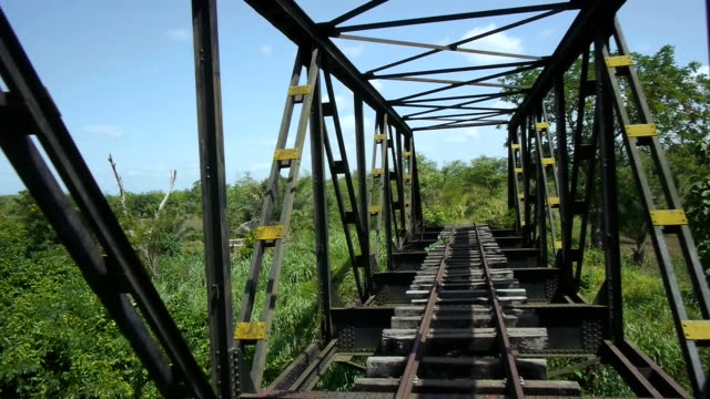 drone shot flying through a disused metal rail bridge in togo. - metal clip stock videos and b-roll footage