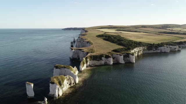 drone shot flying towards a jet ski at the bottom of old harry rocks, dorset, england, united kingdom - eroded stock videos & royalty-free footage