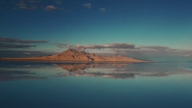 drone shot flying towards a mountain across the flooded bonneville salt flats, utah, united states of america - bonneville salt flats stock videos & royalty-free footage