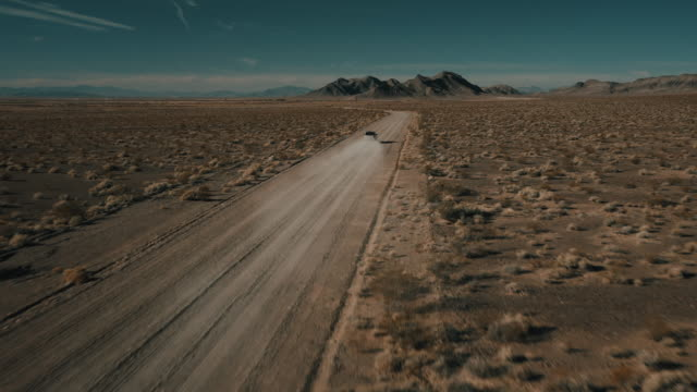 drone shot flying towards a truck driving down a remote dusty road, nevada, united states of america - power in nature stock videos & royalty-free footage