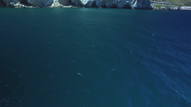 stockvideo's en b-roll-footage met drone shot flying towards sea caves at the base of the rock of gibraltar. - gibraltar iberisch schiereiland