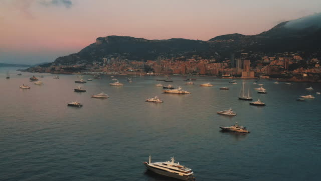 drone shot flying towards super-yachts moored in the bay at sunset during the monaco yacht show 2019 - reportage stock videos & royalty-free footage