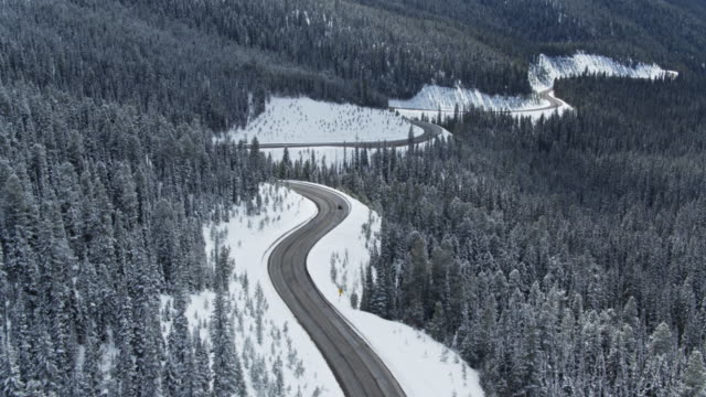 drone shot following car through mountains in snow - mountain pass stock videos & royalty-free footage