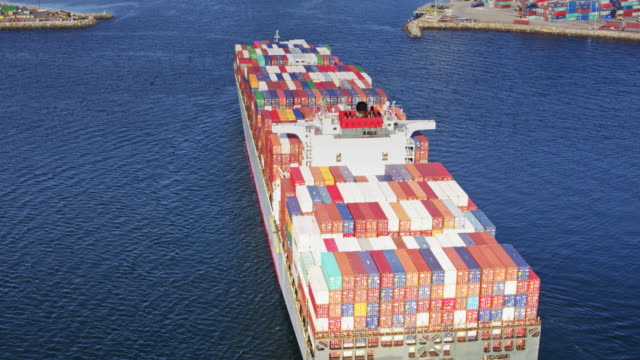 drone shot following cargo ship into port - cargo container stock videos & royalty-free footage
