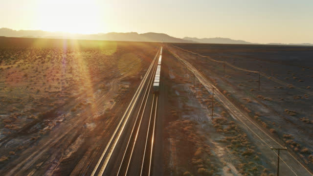 drone shot following freight train across desert - treno video stock e b–roll
