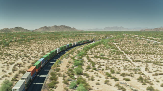drone shot following freight train across desert - cargo train stock videos & royalty-free footage