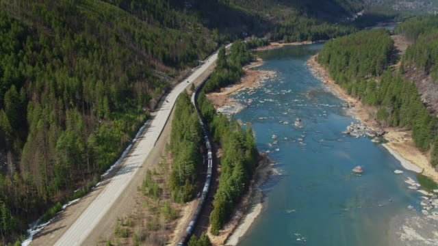 drone shot following freight train between us-2 and kootenai river in northern montana - cargo train stock videos & royalty-free footage