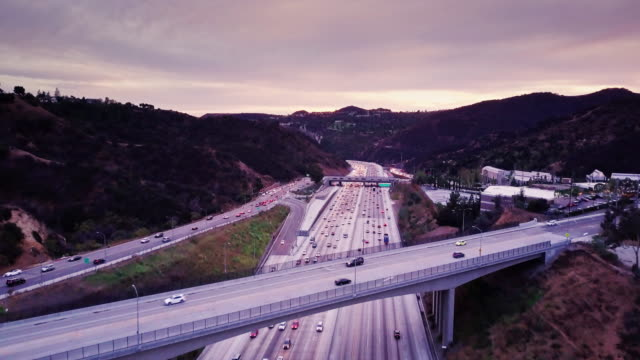 drone shot following i-405 traffic through hills in la - american interstate stock videos & royalty-free footage