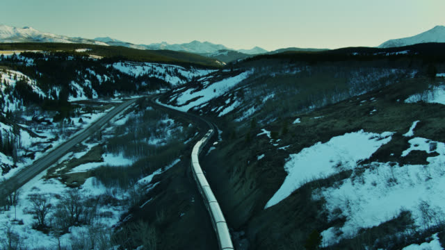 drone shot following passenger train across remote montana landscape - glacier national park us stock videos and b-roll footage