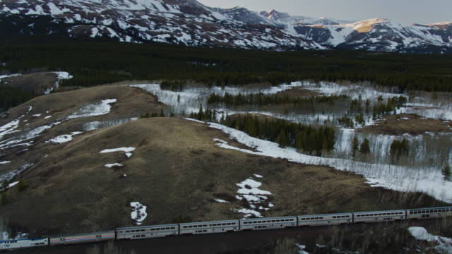 drone shot following passenger train in montana - glacier national park us stock videos and b-roll footage