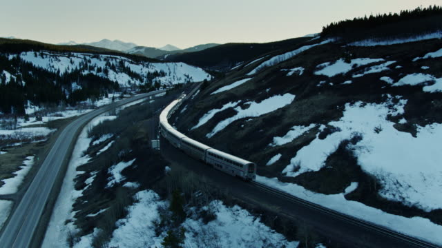 stockvideo's en b-roll-footage met drone shot volgende passagierstrein door mountain pass in montana - locomotief