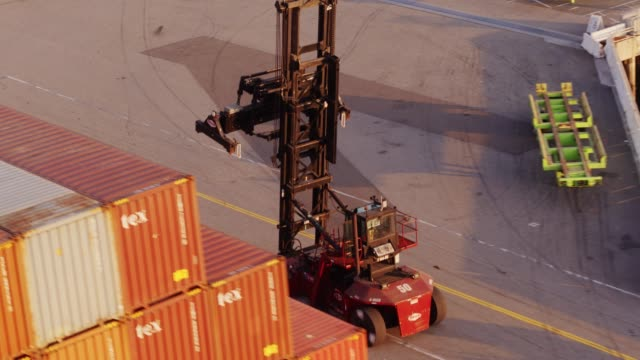 drone shot following top handler through container terminal - box container stock videos & royalty-free footage