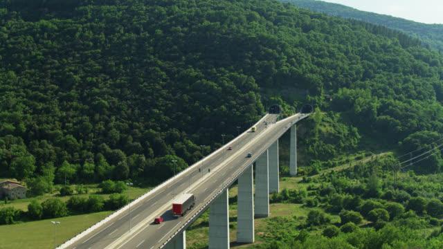 colpo di drone dopo traffico sul ponte verso tunnel vicino a castellfollit de la roca - roca video stock e b–roll