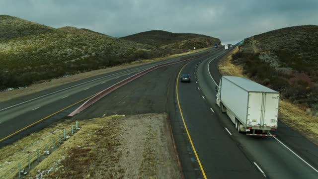 drone shot following truck up hill on interstate in west texas - american interstate stock videos & royalty-free footage