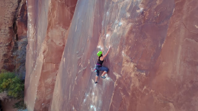 drone shot follows female rock climber as she carefully ascends sandstone rock face in moab. - safety harness stock videos & royalty-free footage