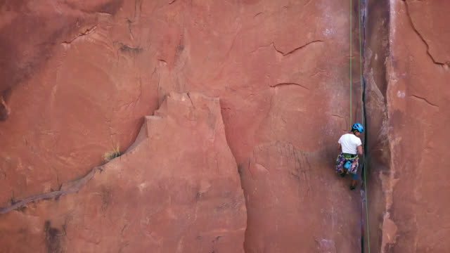 drone shot follows intrepid rock climber rappelling down sandstone rock face to the waiting belayer below. - abseiling stock videos & royalty-free footage