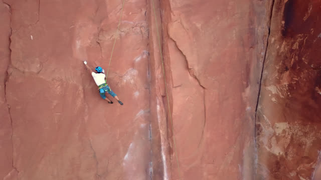 drone shot follows rock climber as he attempts to stretch out on rock face a takes a short fall. - fallimento video stock e b–roll