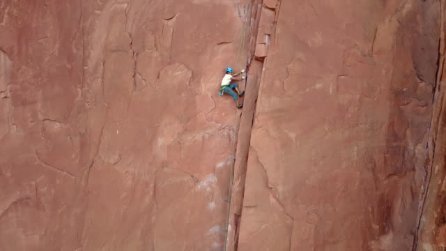 drone shot follows skilled rock climber as he ascends to the top of climbing route on sandstone rock face in moab. - utah stock videos & royalty-free footage