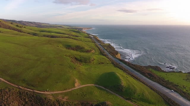 Drone Shot High: Green rolling hills near the coast