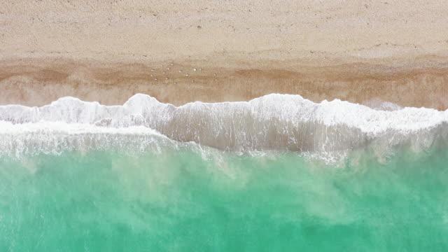 drone shot hovering above waves washing onto brighton beach, england, united kingdom - brighton england stock videos & royalty-free footage