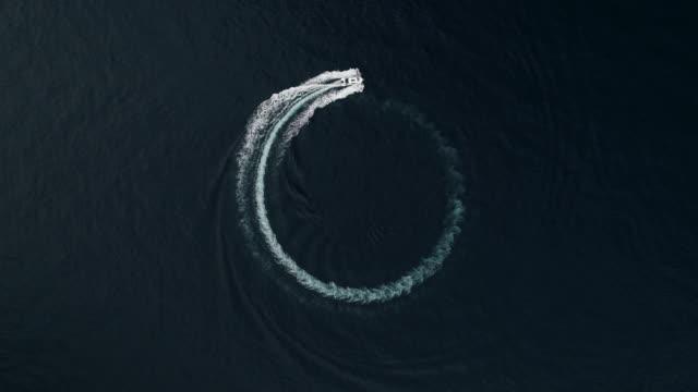 drone shot looking down on a boat drawing a circle in the mediterranean sea, monaco - barca da diporto video stock e b–roll