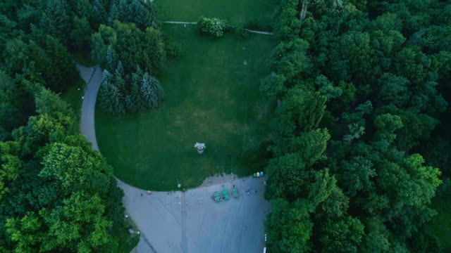drone shot looking down on city park and then revealing beautiful city mountain view - bulgaria stock videos & royalty-free footage