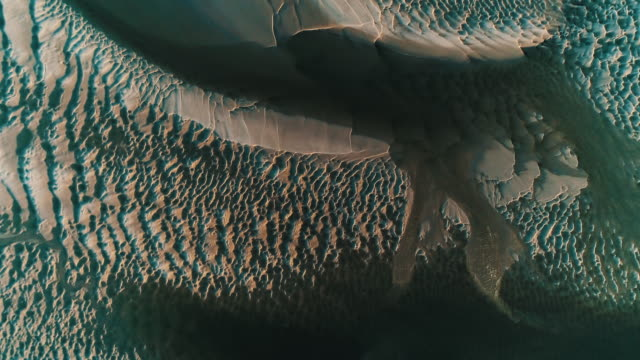 drone shot looking down on sand and water patterns at low tide, borth-y-gest, wales, united kingdom - low tide stock videos & royalty-free footage
