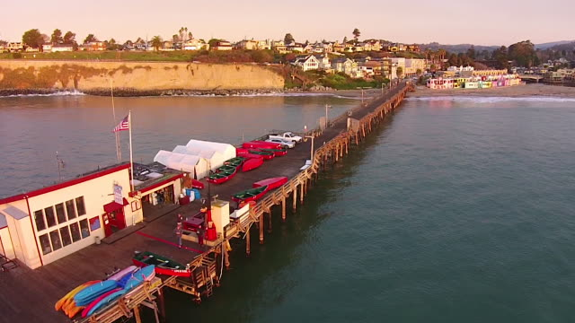 drone shot low: capitola pier reverse to capitola venetian hotel - santa cruz california stock videos and b-roll footage