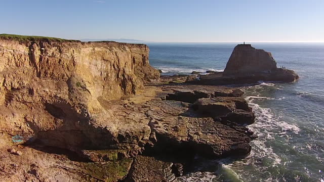 Drone Shot Low: Panther Beach fly-by to couple on sea stack pan-around