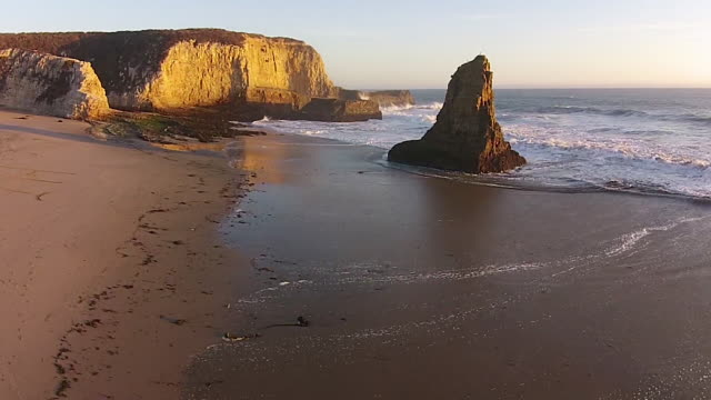 Drone Shot Low to Rise: Davenport Beach fly-by with wave splash