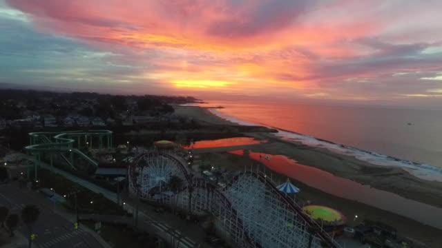 drone shot med to low: sunrise at santa cruz beach boardwalk - カリフォルニア州サンタクルーズ点の映像素材/bロール