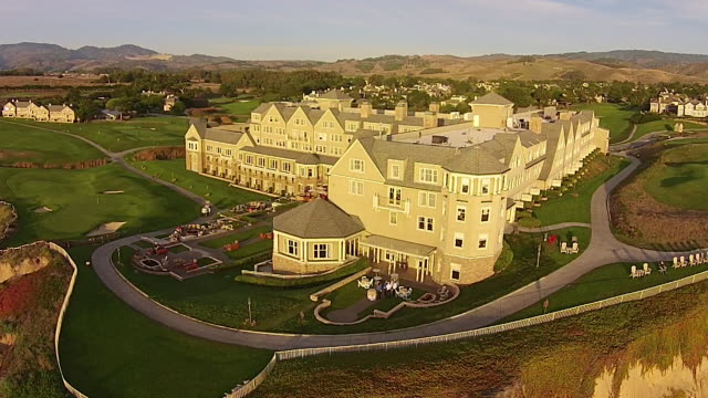 vídeos de stock, filmes e b-roll de drone shot medium reverse pan: ritz-carlton half moon bay - ritz carlton hotel
