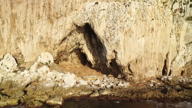 Drone shot moving away from Gorham's Cave at the base of the Rock of Gibraltar.