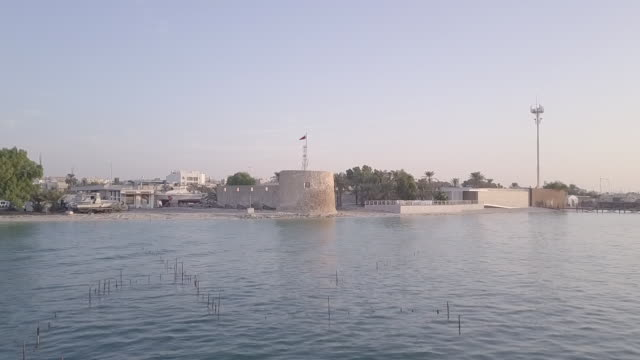 drone shot moving fast over the gulf sea towards and then above bu maher fort. - ペルシャ湾点の映像素材/bロール