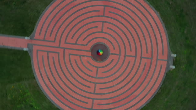 drone shot moving up and rotating whilst looking down on a person spinning an umbrella at the centre of a circular floor pattern, rioja, spain - aerial stock videos & royalty-free footage