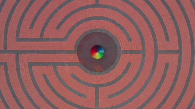 drone shot moving up whilst looking directly down towards a person spinning an umbrella standing at the centre of a strange floor pattern, spain - part of stock videos & royalty-free footage