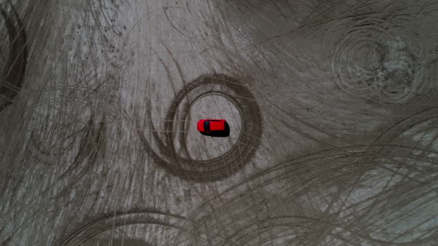 drone shot moving up whilst looking down on a car surrounded by a circular tyre imprint on a beach, france - abstract stock videos & royalty-free footage