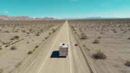 Drone shot of a camper driving over an endless road in the desert