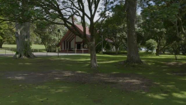 stockvideo's en b-roll-footage met drone shot of a carved maori meeting house in the waitangi treaty grounds - bay of islands nieuw zeeland