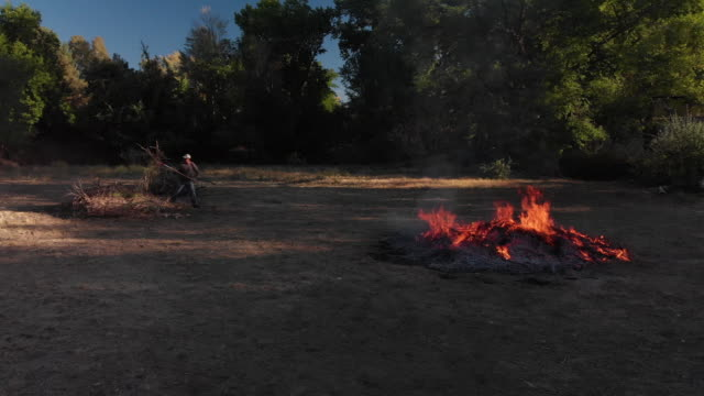 drone shot of a caucasian man in his forties picking up wooden sticks and branches with a pitchfork and throwing them on to a large flaming burn pile with a pitchfork outdoors - pitchfork stock videos & royalty-free footage