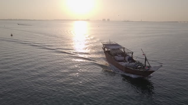 drone shot of a dhow on the gulf sea at sunset. - ダウ船点の映像素材/bロール