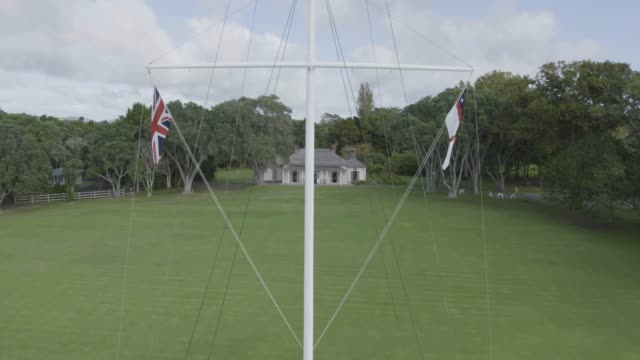 drone shot of a flagpole in the waitangi treaty grounds - bay of islands new zealand stock videos & royalty-free footage