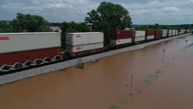 stockvideo's en b-roll-footage met drone shot of a freight train traveling along a flooded landscape in tulsa oklahoma - environment or natural disaster or climate change or earthquake or hurricane or extreme weather or oil spill or volcano or tornado or flooding