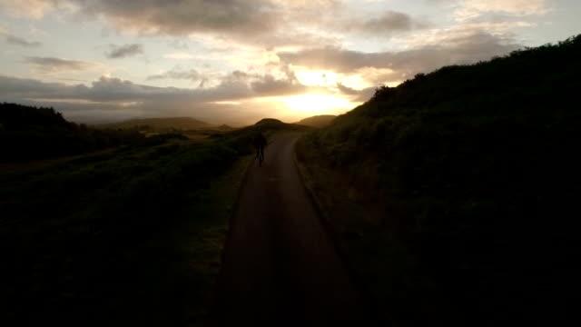vídeos de stock e filmes b-roll de drone shot of a man cyling along a quiet road in scotland during sunrise - ciclo
